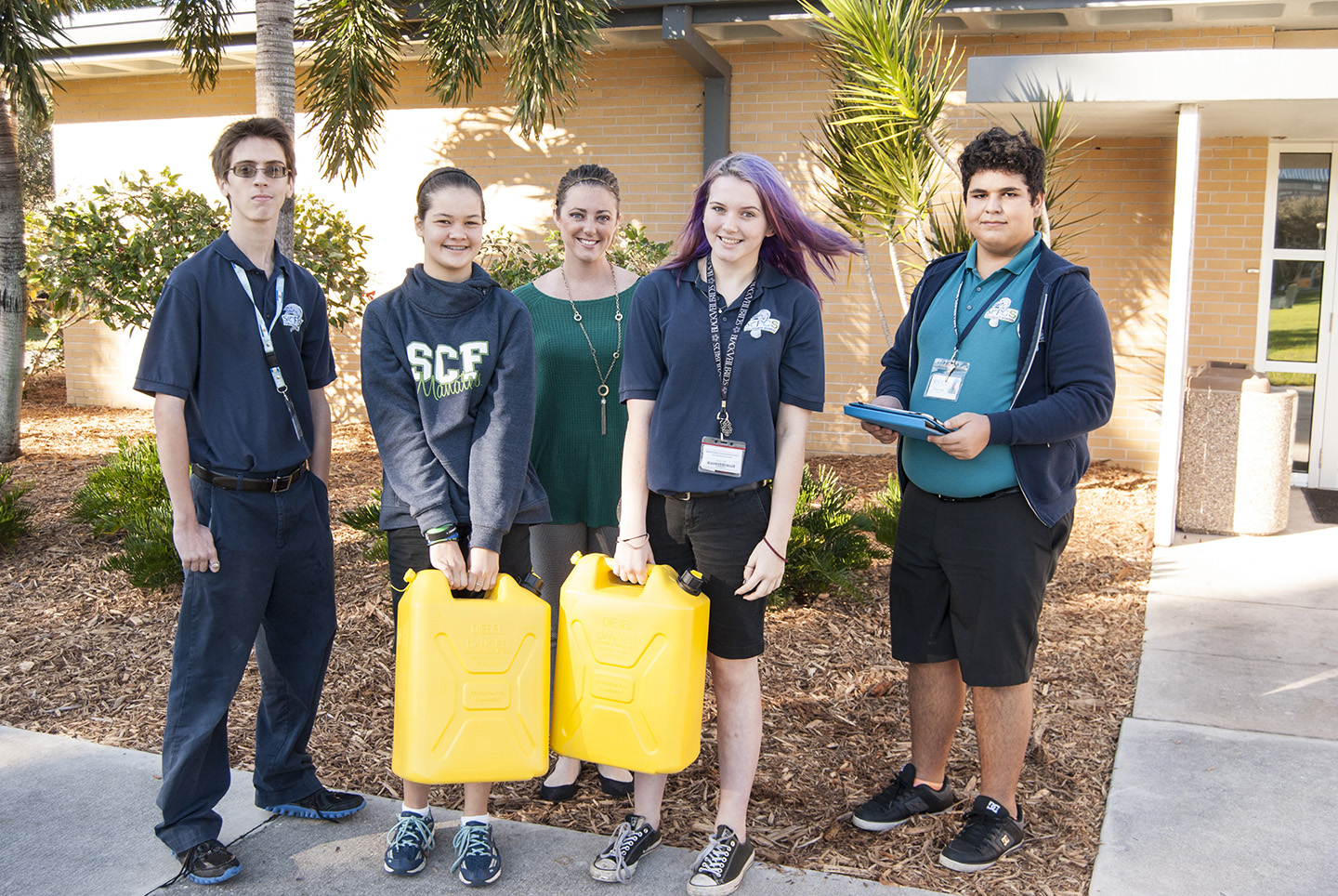 State College of Florida Collegiate School 8th-graders Eric Long, Kea Kamiya, Julie Stivers and Ismael Ruiz with teacher Hannah Cochrane (in back) show the cans of water students carried with them to class.