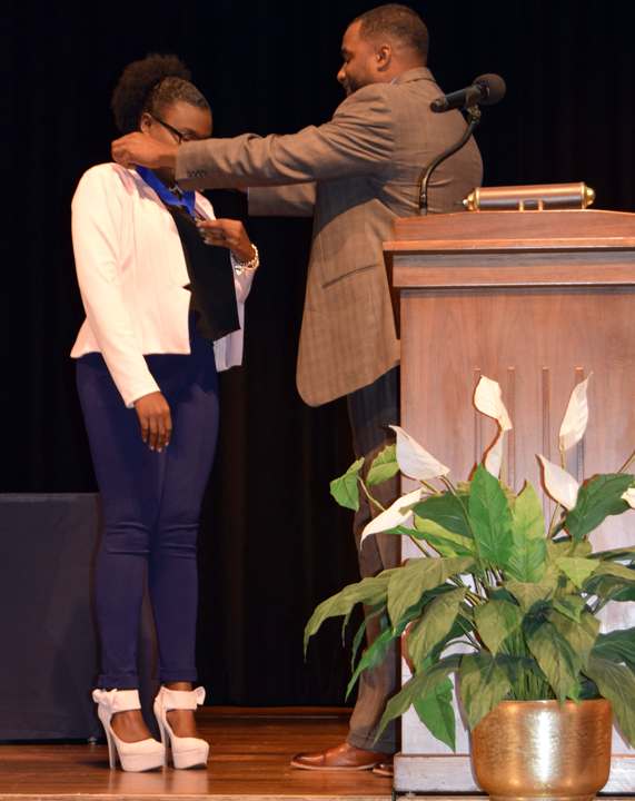 1. Dwight Gilmer of Southeast present Catelaine Laguerre with the Student of the Year Medal.