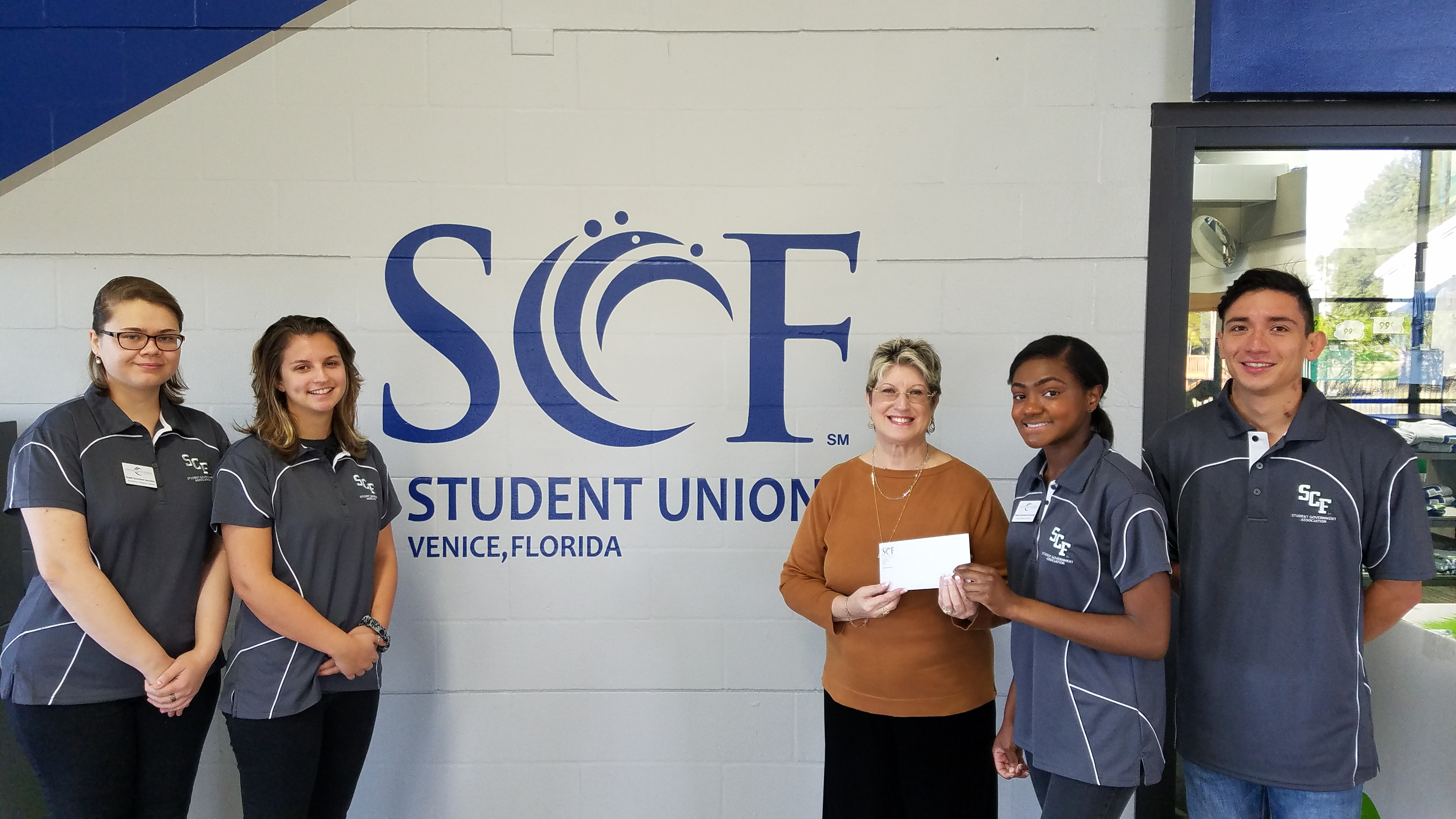 Venice SGA presenting check to Reins Inspiring Change trustee Maria Kalapati.