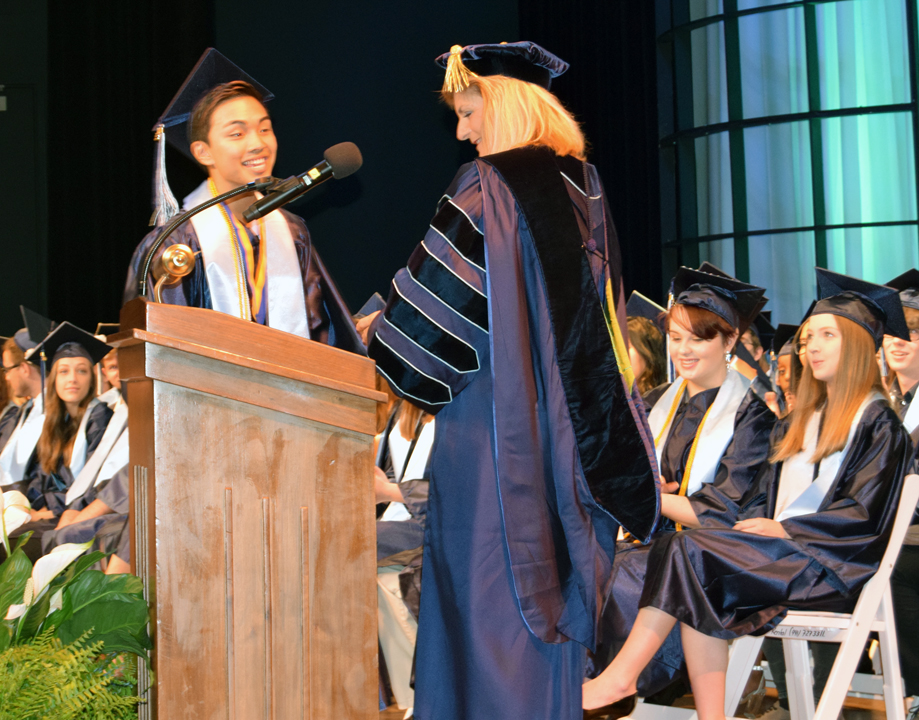 Dr. Carol F. Probstfeld SCF president, presents the Outstanding Graduate Award to Ronan Bustamante.
