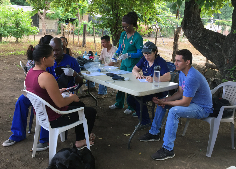 The medical team performs triage for a villager.