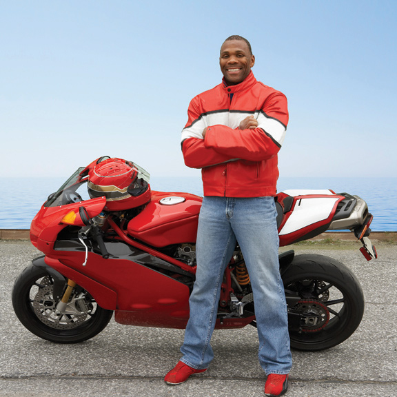 Man in a red jacket standing in front of a red motorcycle
