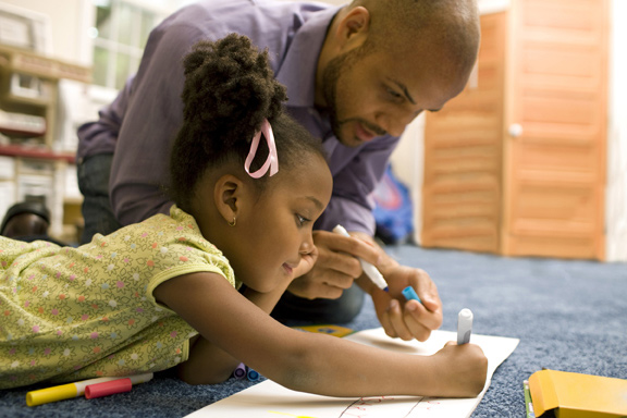 Parent helping a girl drawing on paper
