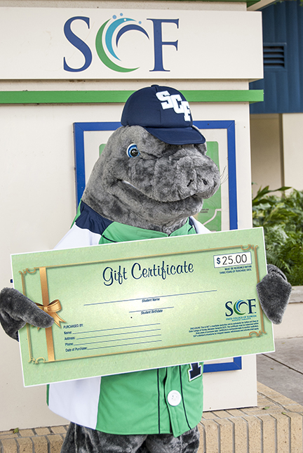 SCF mascot Maverick the Manatee shows off the gift certificates now being sold by SCF so that friends and family can help new and returning students pay for tuition and fees.